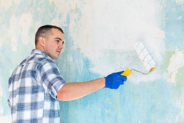 Mężczyzna pracuje na ścianie z farba rolownikiem