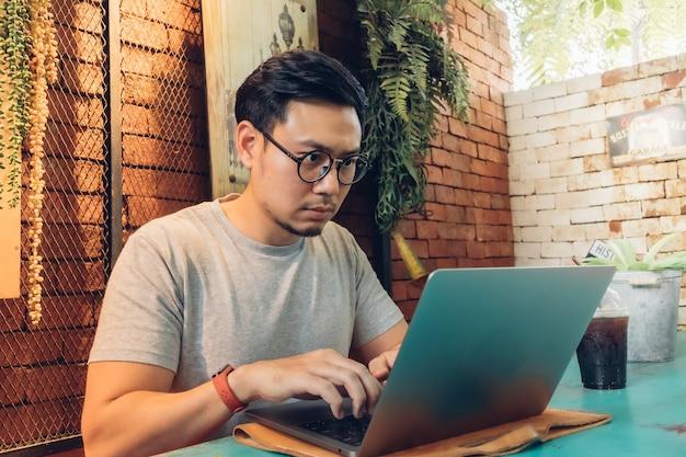 Mężczyzna pracuje na swoim laptopie w kawiarni.