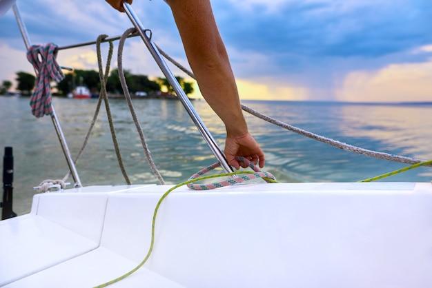 Mężczyzna pracuje na żaglówce i lubi uprawiać sport żeglarski, żeglując po oceanach