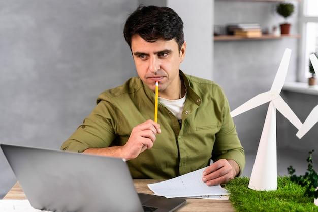 Mężczyzna pracuje nad projektem ekologicznej energii wiatrowej i myśli trzymając ołówek