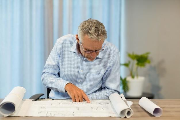Mężczyzna pracuje nad projektem przy jego biurkiem