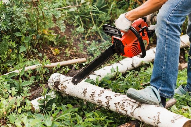 Mężczyzna pracuje nad stworzeniem domu, piłowaniem drewna, budową, piłą, piłą mechaniczną, dłutem, gwoździami, śrubami