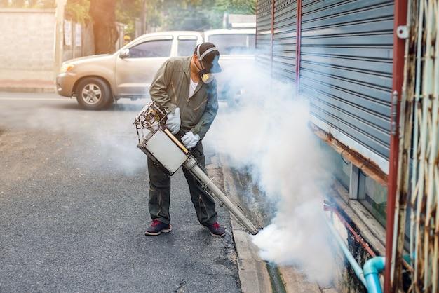 Mężczyzna pracuje nad zamgleniem, aby wyeliminować wirusa komara i wirusa zika