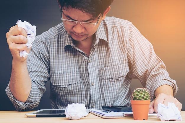 Mężczyzna pracuje poważnie z zmiętym papierem w jego ręce