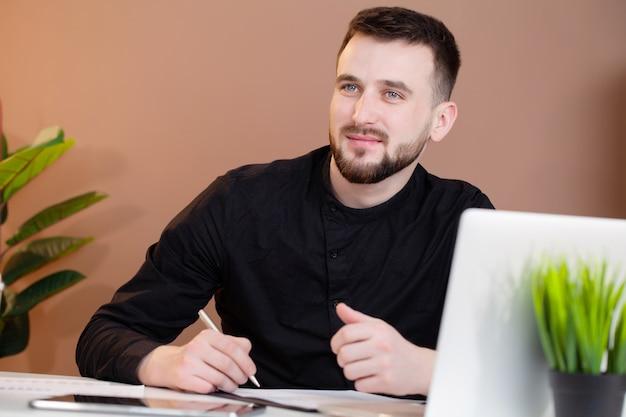 Mężczyzna pracuje przy biurem na laptopie