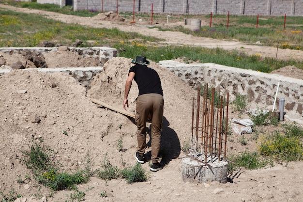 Mężczyzna pracuje przy budowie parterowego domu