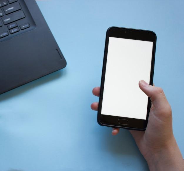 Mężczyzna pracuje przy laptopie i płasko trzyma telefon w dłoni. problem koncentracji w pracy podczas pracy w domu. mężczyzna rozproszony przez telefon podczas pracy w domu na laptopie.