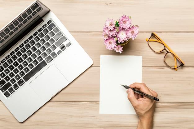 Mężczyzna pracuje przy stołem z pustym papieru prześcieradłem i notatnikiem