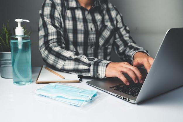 Mężczyzna pracuje w biurze w domu, aby chronić się przed chorobą coronavirus lub covid-19.