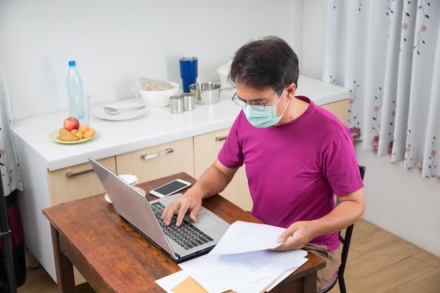 Mężczyzna pracuje w domu, aby chronić infekcję koronawirusem (covid-19) z zewnątrz