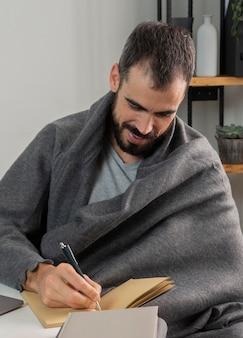Mężczyzna pracuje w domu i pisze w zeszycie