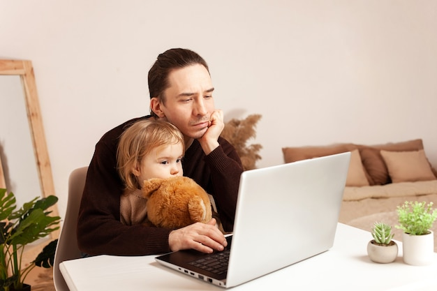 Mężczyzna pracuje w domu na laptopie, dziecko odwraca uwagę od pracy, tęskni za ojcem i córką