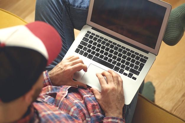 Mężczyzna pracuje w domu z laptopem.