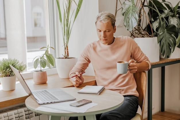 Mężczyzna pracuje w miejscu pracy z dokumentami i pije kawę w ekologicznej kawiarni z roślinami