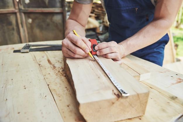 Mężczyzna pracuje w sklepie stolarskim, pracuje z drzewem.