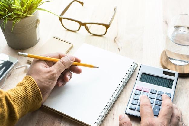 Mężczyzna pracuje z kalkulatorem i notatnikiem na stole roboczym
