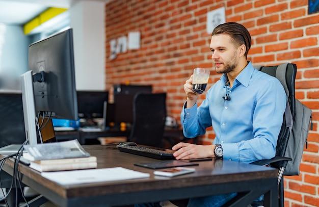 Mężczyzna pracuje z komputerem przy firmy biurem.