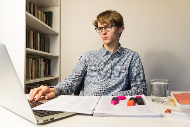 Mężczyzna pracuje z książkami i laptopem na zlecenie domu