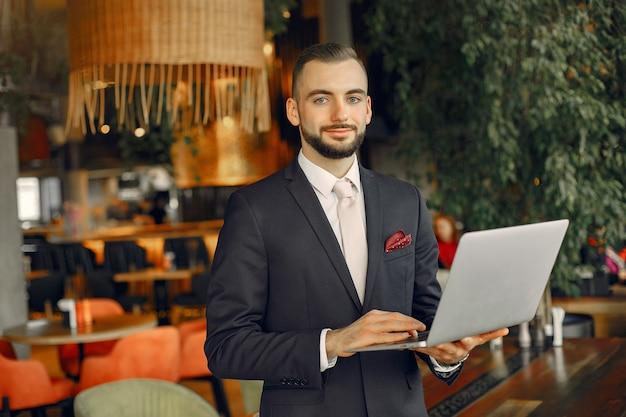 Mężczyzna pracuje z laptopem przy stołem