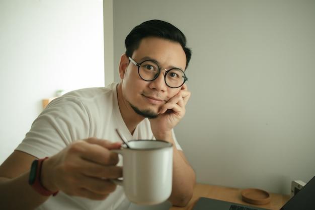 Mężczyzna pracuje z laptopem w swoim mieszkaniu w koncepcji work from home.