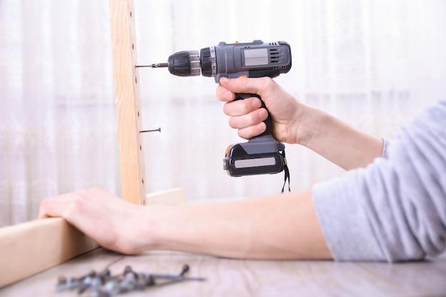 Mężczyzna pracuje z montażem mebli przy użyciu elektrycznego śrubokręta w instalacji nowego domu - technik przy pracy przy użyciu narzędzi ręcznych