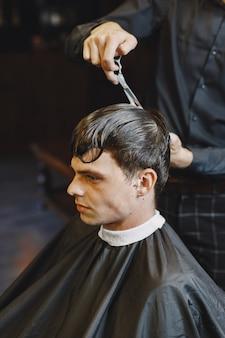 Mężczyzna pracuje z włosami. fryzjer z klientem.
