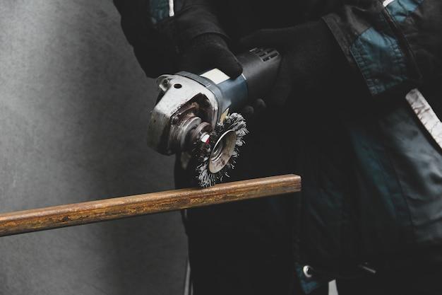 Mężczyzna pracuje ze szlifierką kątową. proces szlifowania metalu
