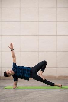 Mężczyzna praktykuje jogę na macie na zewnątrz z miejsca na kopię