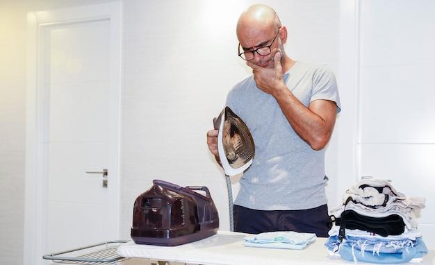 Mężczyzna prasowanie gospodarstwa domowego. robi prace domowe. copyspace