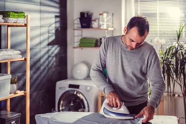 Mężczyzna prasowanie odziewa w domu