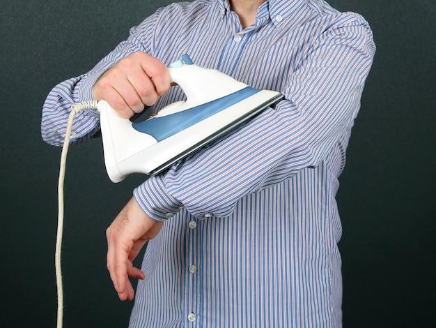 Mężczyzna prasuje koszulę na dłoni