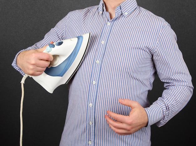 Mężczyzna prasuje koszulę na piersi