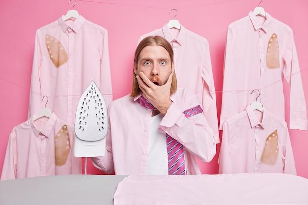 Mężczyzna prasuje prane ubrania żelazkiem na desce do prasowania wady wpatrują się w usta z wyrazem omg sukienki do pracy otoczone koszulami