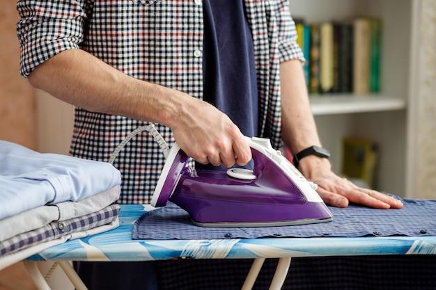 Mężczyzna prasuje żelazkiem koszulę na desce do prasowania