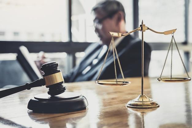 Mężczyzna prawnik lub sędzia pracujący z dokumentami kontraktowymi, książkami prawniczymi i drewnianym młotkiem na stole w sali sądowej