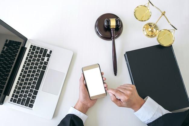Mężczyzna prawnik lub sędzia pracuje z inteligentnego telefonu i skale sprawiedliwości, książek prawa, młotek