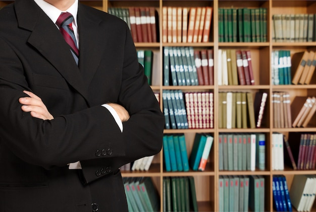 Mężczyzna prawnik w bibliotece na półkach z książkami w tle