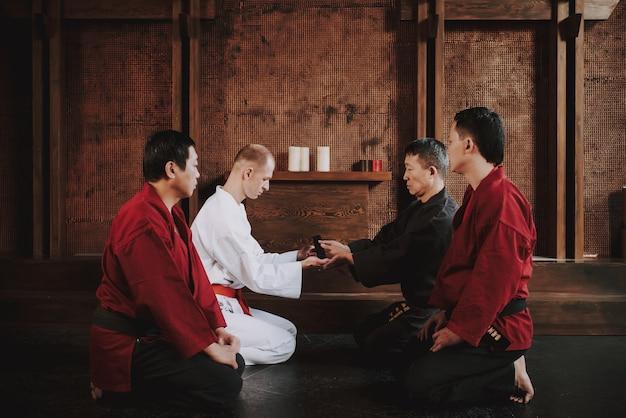 Mężczyzna prezentuje wojownika sztuk walki w kolorze białym.