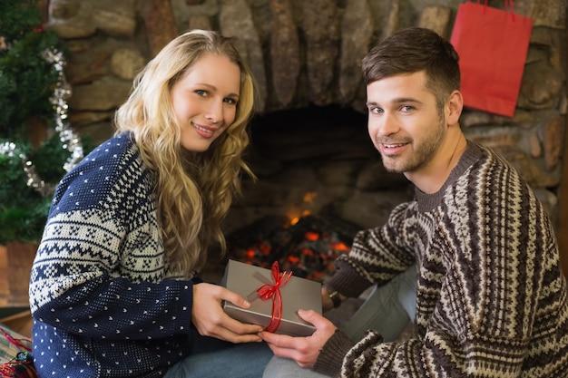 Mężczyzna prezenty kobieta z przodu oświetlonej kominki podczas bożego narodzenia