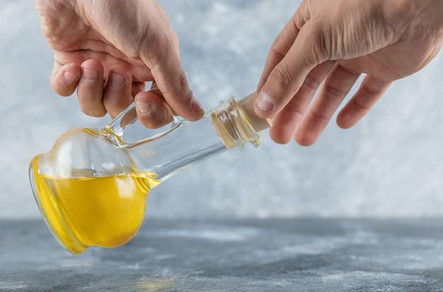 Mężczyzna próbuje otworzyć butelkę oleju. wysokiej jakości zdjęcie