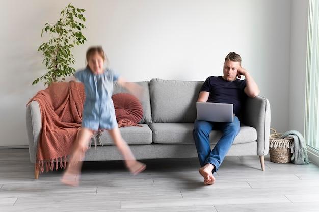 Mężczyzna próbuje pracować na laptopie w domu, podczas gdy jej dzieci biegają dookoła