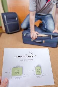 Mężczyzna próbuje zamknąć pełny bagaż podręczny, aby spełnić ograniczenia tanich linii lotniczych