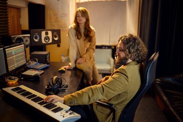Mężczyzna producent i wokalistka, wnętrze studia nagrań na tle. syntezator i mikser audio, miejsce pracy muzyków, proces twórczy