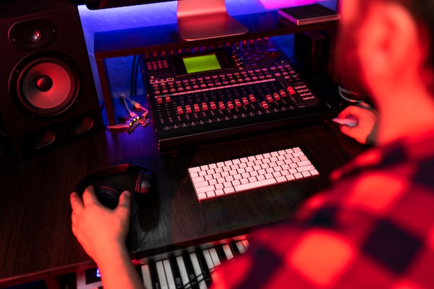 Mężczyzna producent pracuje nad mikserem z dźwiękiem i ścieżką w studiu nagraniowym.