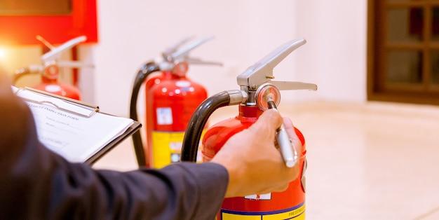 Mężczyzna profesjonalna inspekcja gaśnica, koncepcja bezpieczeństwa.