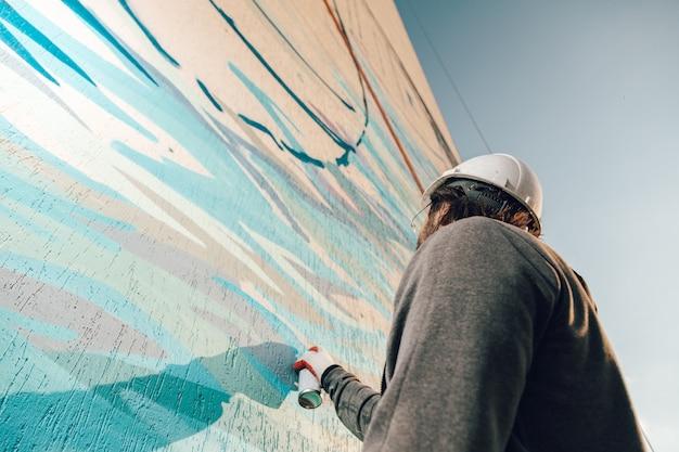 Mężczyzna profesjonalny malarz-budowniczy maluje ścianę nowego budynku