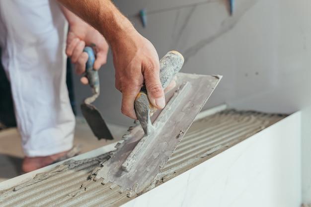 Mężczyzna profesjonalny pracownik montuje płytki ceramiczne na zdjęciu w łazience za pomocą bliskiej szpachelki z klejem