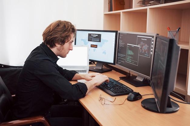 Mężczyzna programista pracujący na komputerze stacjonarnym z wieloma monitorami w biurze w firmie programistycznej. technologie programowania i kodowania stron internetowych