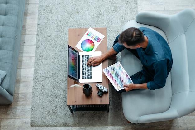 Mężczyzna projektant pracuje w domowym biurze ludzi i technologii