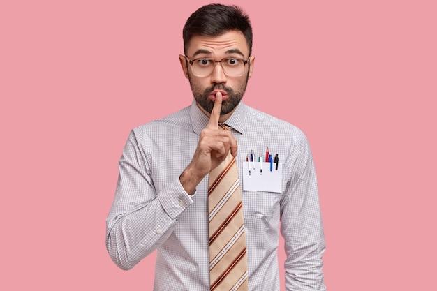 Mężczyzna projektant trzyma palec na ustach, ubrany w formalny strój, ma w kieszeni koszuli pustą kartkę z ołówkiem i długopisami